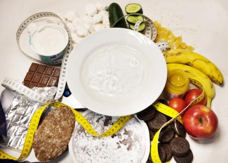 Pöydällä on syvä lautanen, jossa on ilmeisesti vettä. Sen ympärillä on avattu suklaalevy, avattu maitorahkapurkki, ruisleipä, omenoita, banaaneja, kurkku, suklaakakku, avattu pilttipurkki, marenkeja ja keksejä. Kaiken keskellä kiemurtelee mittanauha.
