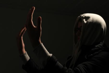 Tummassa kuvassa huppupäinen henkilö on nostanut kätensä kasvojen korkeudelle. Kuvan ulkopuolelta tuleva valo piirtää esiin kämmenten ääriviivat.