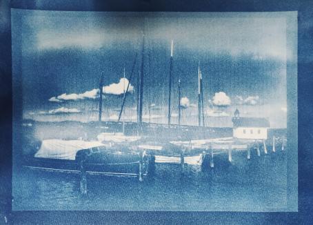 Sinisävyisessä, rakeisessa kuvassa on satamassa veneitä. Taivaalla on valkoisia kumpupilviä.
