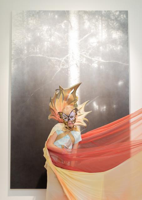 Mustavalkoisen, puuta esittävän taideteoksen edessä seisoo henkilö, jolla on perhoskasvonaamari silmien päällä, jonkinlainen iso kaulus joka kaartuu pään taakse ja vartalon ympärillä keltaista ja punaista kangasta joka jatkuu kuvan ulkopuolelle.
