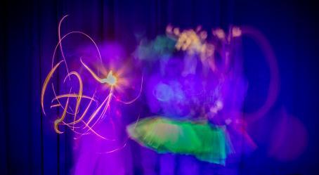 Maahan asti ulottuvan verhon edessä on liike-epäteräviä hahmoja ja valoviivoja. Toisella hahmoista on vihreä hame. Kuva on sinisävyinen.