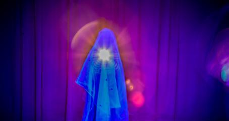 Maahan asti ulottuvan verhon edessä on läpikuultavan kankaan alla ihmisen hahmo, joka osoittaa taskulampulla kameraan. Kuva on sinisävyinen.