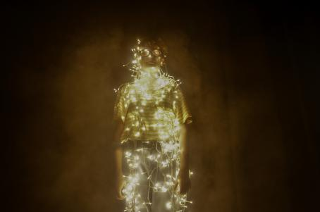 T-paitaan ja farkkuihin pukeutunut henkilö on kääritty led-valonauhoihin. Valonauhat valaisevat kuvan, ja ympäristö on tumma.