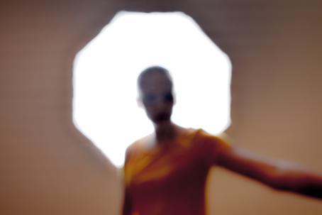 Epäterävässä kuvassa henkilö seisoo kirkkaan monikulmaisen lampun edessä. Hän ojentaa toista kättään sivulle kuvan ulkopuolelle.