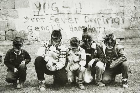 Mustavalkoisessa kuvassa viisi poikaa on osittain polvillaan, osittain kyykyssä maassa. Heidän kasvonsa on sotkettu mustalla kuvan päälle. Heidän takanaan on muuri, johon on kirjoitettu jotain.