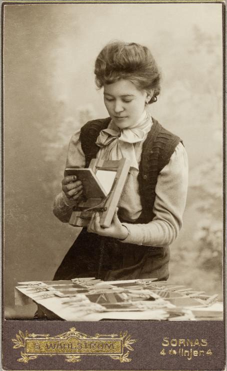 Valokuvaaja Olga Albinson (myöh. Hart) tutkii päivänvalokehystä. Pöydällä hänen edessään on riveissä pyykkipojilla kiinnitettyjä lasilevyjä. Joseph Hart, Atelier Wahlström, n. 1907 / Suomen valokuvataiteen museon kokoelma.