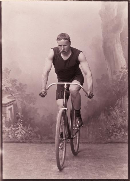 Studiossa kuvattu muotokuva J.K. Lindstedtistä, kirjakauppiaasta ja ansioituneesta kilpapyöräilijästä Whitworth- pyöränsä selässä. Lindstedt on pukeutunut Helsingin pyöräilyklubin varusteisiin.Tuntematon kuvaaja, 1894 / Suomen valokuvataiteen museon kokoelma.