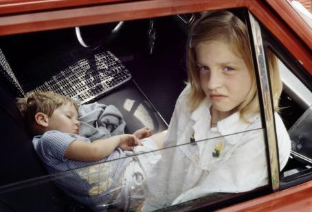 Punaisen auton etupenkillä on kaksi lasta. Isompi tyttö istuu ja katsoo puoliksi auki olevasta ikkunasta kameraan, pienempi poika nukkuu maaten penkillä.