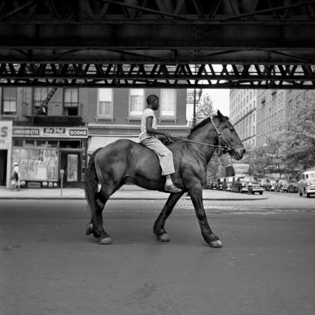 Mustavalkoisessa kuvassa tummaihoinen mies ratsastaa tummalla hevosella kaupungin kadulla. Hevosella ei ole satulaa, vain suitset.