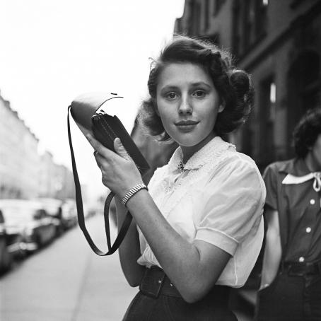 Mustavalkoisessa kuvassa nuori nainen katsoo suoraan kameraan. Nainen pitelee käsissänsä pientä käsilaukkua. Hänellä on lyhyehköt kiharat hiukset, valkoinen paita, iso vyö ja hame tai housut.