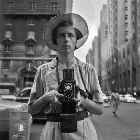 Mustavalkoinen kuva hattupäisen naisen heijastuksesta. Nainen pitää molemmin käsin Rolleiflex-kameraa ja katsoo hieman yläviistoon.