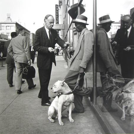 Mustavalkoisessa kuvassa tummaihoinen mies nojaa rakennuksen seinään ja pitää kädessään mukia. Valkoihoinen vanhempi mies on juuri laittamassa mukiin jotain. Tummaihoisen miehen vieressä on valkoinen koira, jonka hihna hänellä on kädessä.