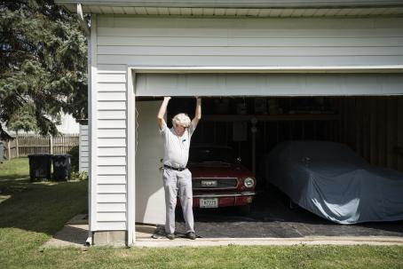 A white man standing underneath a garage door. His hands are raised and he's just either closing or opening the door. There are two cars in the garage, the other is covered with fabric.