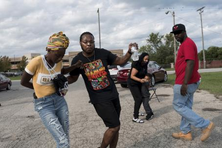 Black people outside in something that looks like a parking lot. In the front there are two people next to each other, like frozen in the middle of dancing. On the right side a man is walking by and looking at the camera. Behind them are a woman and a child, who look like they are dancing. In the background there are parked cars.