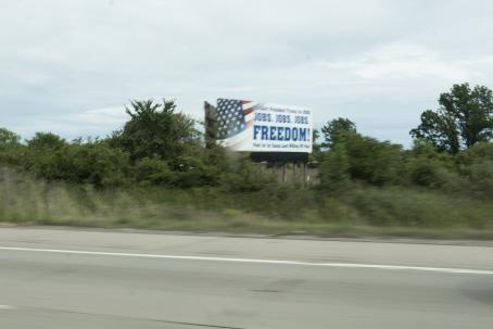 A blurry photo, that has probably been taken from a moving car. Next to the road, in the middle of vegetation, there is an ad etc. that has the USA flag and text: Jobs! Jobs! Jobs! FREEDOM!