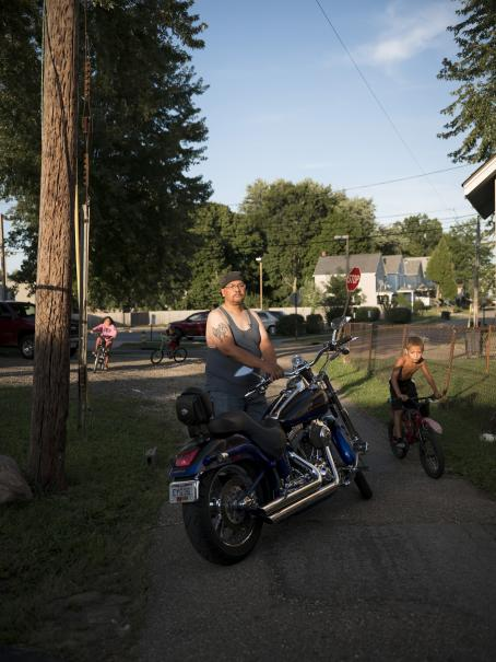 A white man stands on a sidewalk or a driveway. In front of him is a motorcycle, he has his hand on the handle. Behind him there are children on their bikes.