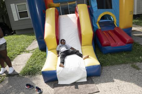 A black child is laying at the end of the slide of a bouncing castle. It looks like he is wearing white eye make-up.
