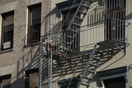 A fire escape staircase in the wall of an apartment building. Two people are sitting at the base of the stairs, probably enjoying the sunshine.
