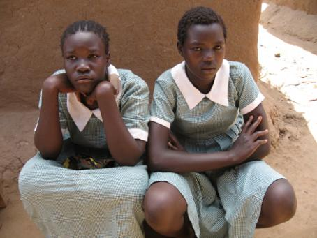 Kaksi tummaihoista tyttöä istuu vierekkäin. Heillä on päällään vihreäsävyiset vaatteet joissa on valkoiset kaulukset.
