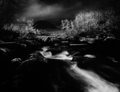 Mustavalkoinen, tummasävyinen maisemakuva. Keskellä virtaa puro muuta kuvaa vaaleampana.