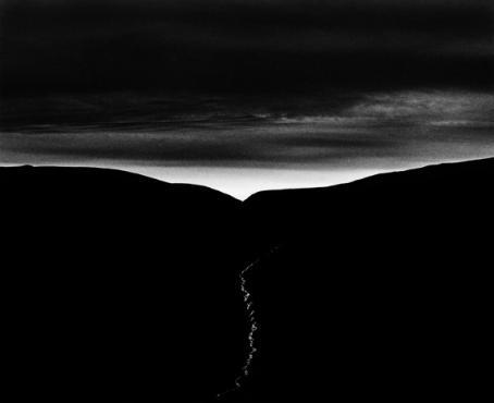 Mustavalkoinen, tumma kuva. Keskellä musta alue, jonka yläpuolella kaistale vaaleampaa.