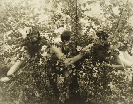 Koivikossa pienten koivujen takana on kolme alastonta ihmistä.