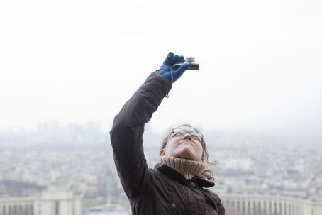 Silmälasipäinen nainen pitelee kameraa ylhäällä ja katsoo siihen. Hänen taustallaan näkyy kaupungin rakennuksia.