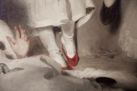 Jalat joissa on valkoiset sukkahousut ja punaiset kengät. Niiden yläpuolella näkyy osa valkoisesta mekosta. Etualalla olevasta valkoisesta kankaasta nousee käsi.