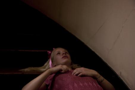 Tyttö makaa lattialla. Hänellä on hiuksissa vaaleanpunainen rusetti ja päällään vaaleanpunainen paita.