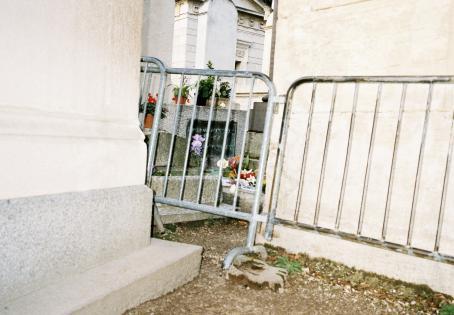 Metalliaitaa, jonka takana näkyy kahden rakennuksen seinän välistä hautakiviä.