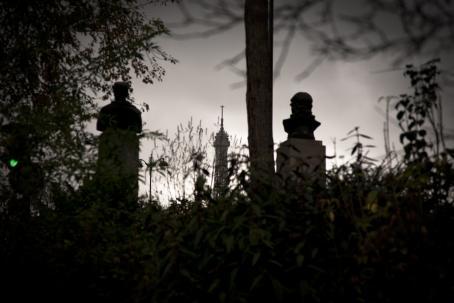 Tummasävyisessä kuvassa näkyy heinikkoa, puita ja taustalla patsaita sekä torni.