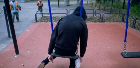 Mustahupparinen hahmo istuu keinussa huppu päässä nojaten eteenpäin.