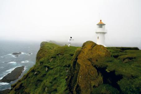 Vihreillä rantakallioilla seisoo valkoasuinen henkilö. Taustalla näkyy valkoinen majakka ja sumuista maisemaa.