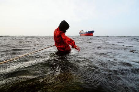 Punatakkinen henkilö seisoo vedessä. Hänessä on kiinni köysi joka katoaa kuvan ulkopuolelle. Kauempana ulapalla näkyy laiva.