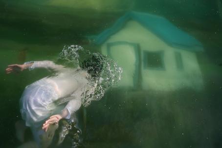 Valkoasuinen hahmo on veden alla. Kuvassa näkyy myös talo.