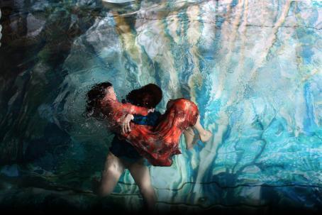 Veden alla on kaksi henkilöä. Taaempi pitää sylissään toista, jolla on punainen mekko.