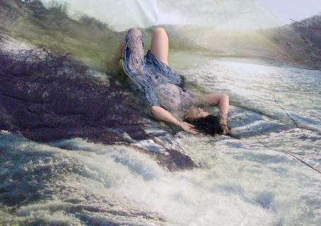 Henkilö makaa osittain veden alla polvet koukussa. Taustalla on vesiputous.