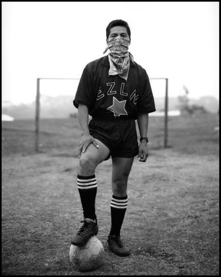 Mustavalkoisessa kuvassa mies seisoo jalkapallomaalin edessä ja pitää jalkaa pallon päällä. Hän on peittänyt suunsa ja nenänsä huivilla.