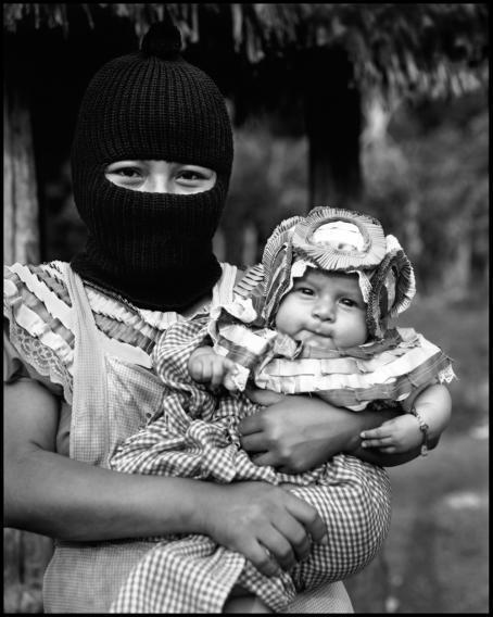 Mustavalkoisessa kuvassa kommandopipoinen nainen pitää sylissään hienosti puettua vauvaa.
