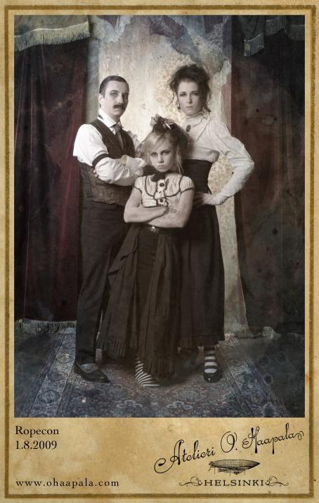 """Kolme henkilöä mustavalkoisissa vaatteissa. Takana raskaat punaiset verhot. Alareunassa on teksti """"Ropecon 1.8.2009""""."""