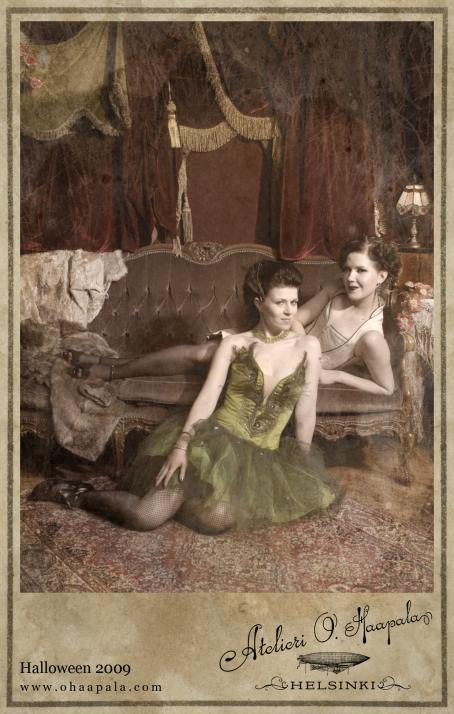 """Kaksi naista, joista toinen makoilee sohvalla ja toinen istuu sohvan edessä. Edessä olevalla on päällään vihreä mekko. Taustalla näkyy raskaat punaiset verhot. Alareunassa on teksti:""""Halloween 2009, Atelieri O.Haapala, Helsinki""""."""