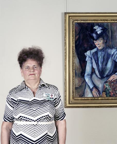 Nainen mustavalkoisessa mekossa seisoo taideteoksen vieressä. Kehystetty taideteos esittää hattupäistä naista.