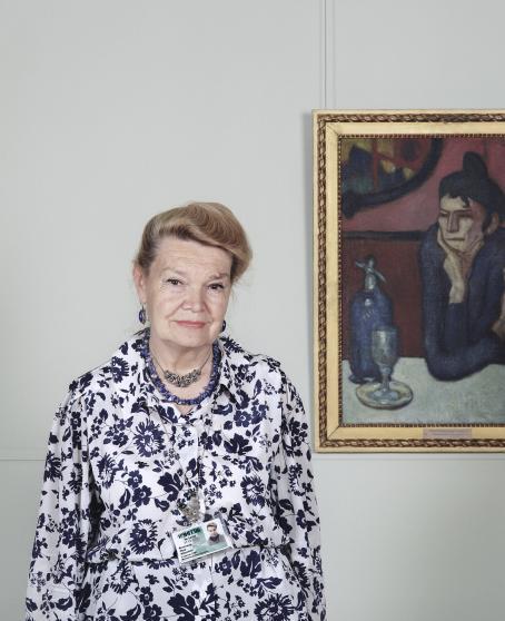Nainen seisoo kukkakuvioisessa paidassa seinällä olevan taideteoksen vieressä. Taideteoksessa on nainen joka nojaa leukaansa kämmeneen.