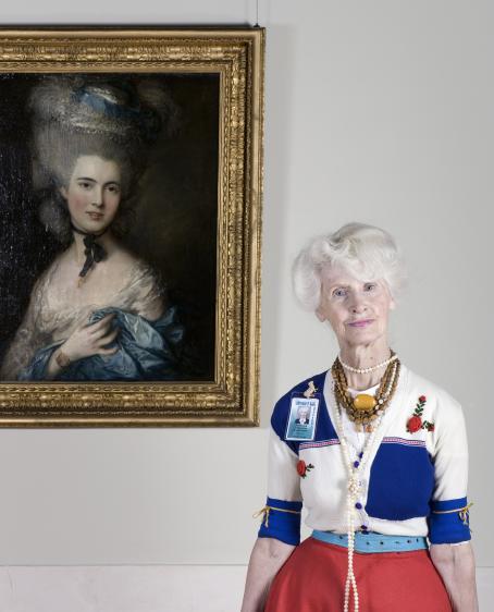 Valkohiuksinen nainen seisoo seinällä olevan taideteoksen vieressä.