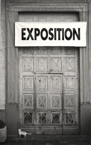 """Mustavalkoisessa kuvassa on ovi ja oven yläpuolella banneri, missä lukee isoilla mustilla kirjaimilla """"exposition"""". Alhaalla oven edessä on valkoinen kissa."""