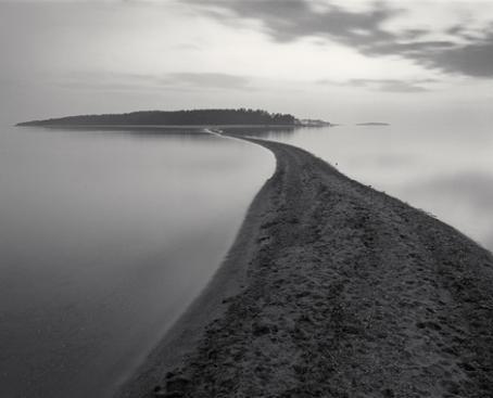 Mustavalkoisessa kuvassa on hiekkasärkkä, joka jatkuu kauempana näkyvää saarta kohti. Särkän ympärillä on tyyni vedenpinta.