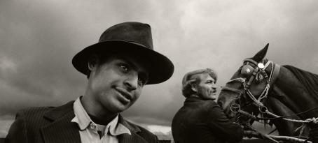 Mustavalkoisessa kuvassa kaksi miestä, joista toinen pitelee hevosta hieman taaempana. Heidän takanaan näkyy vain pilvistä taivasta.