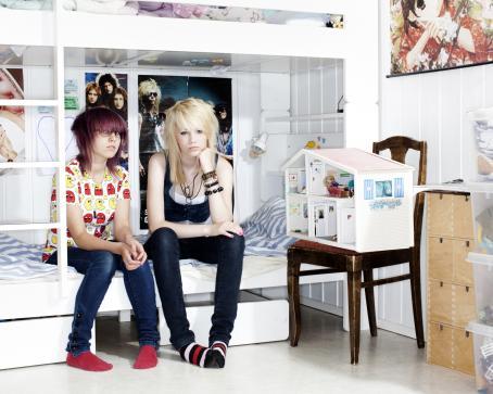 Kaksi nuorta ihmistä istuu kerrossängyn alemmalla sängyllä. Heidän vieressään tuolilla on nukketalo.