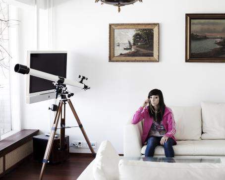 Valkoisella sohvalla istuu nuori nainen, jolla on mustat, pitkät hiukset ja vaaleanpunainen takki.