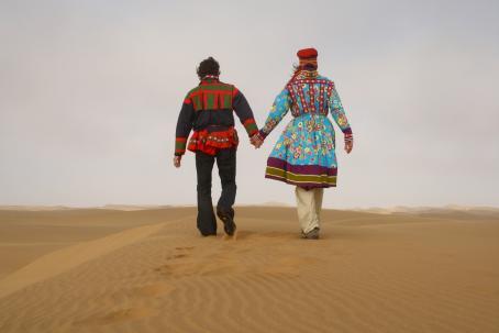 Kaksi henkilöä kävelee käsi kädessä hiekalla aavikolla. Heillä on päällään värikkäät vaatteet.